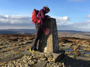Woman using a map and compass at a trig point on Kinder in the peak District